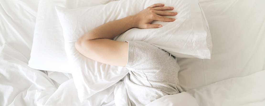 Tired young man in bed closing his ears with pillow trying to sleep. Sleep disorder and problems. Loud noise
